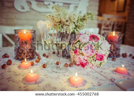Wedding bouquet stands behind champagne flutes on the table decorated with nuts - stock photo