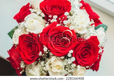 Wedding bouquet. White and red roses. Two wedding rings lie on the flowers.