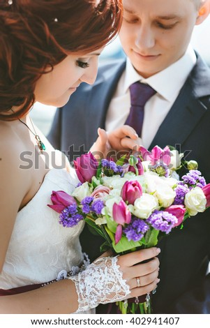 Wedding bouquet, white, pink, purple flowers. In the hands of the bride