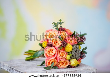 Wedding bouquet with beautiful orange roses and yellow ranunculus lying down isolated on   colorful background - stock photo