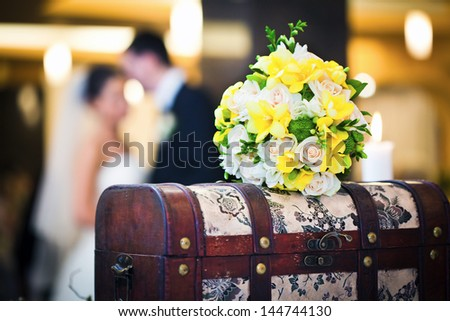 Wedding bouquet with bride and groom blurred in background - stock photo