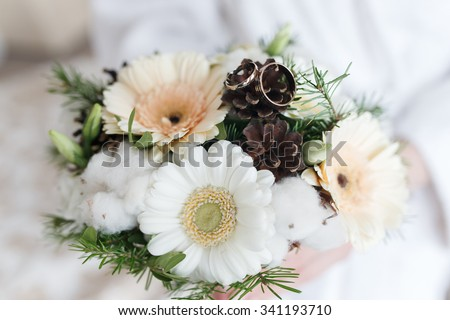wedding bouquet with pine cones. winter wedding bouquet. beautiful gold wedding rings - stock photo