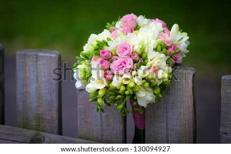 Wedding bouquet with roses and freesia on rustic country fence