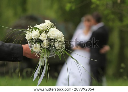 Wedding bouquet with the wedding couple in the background - stock photo