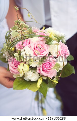 wedding bouquet with wedding rings at bride's hands - stock photo