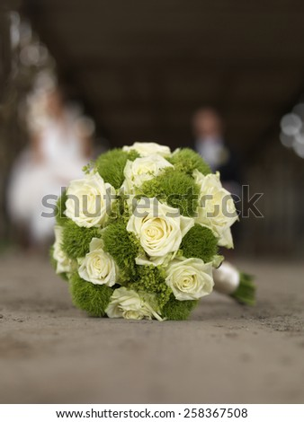 wedding bouquet with white roses, couple vaguely in the background, copy space