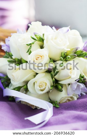 Wedding bouquet with white roses on violet background. Ribbons