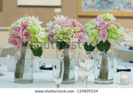 Wedding bouquets on table at reception dinner party - stock photo