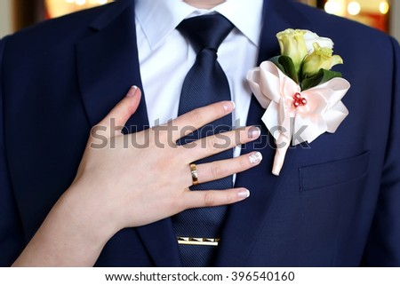 Wedding boutonniere and the hand of bride with ring - stock photo