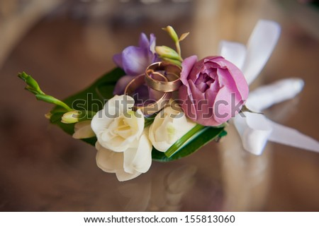 wedding boutonniere and wedding rings - stock photo