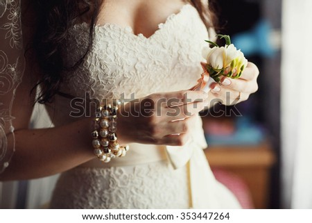 wedding boutonniere in the hands of the bride - stock photo