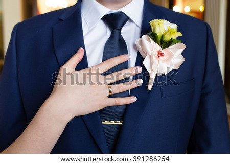 Wedding boutonniere on suit and brideâ??s hand - stock photo