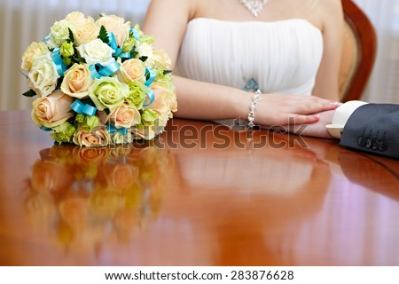 Wedding bridal bouquet is beside the hands newlywed. - stock photo