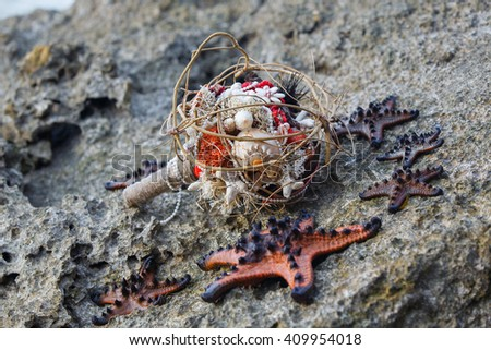 Wedding bridal bouquet made â??â??of shells and pearls and other natural materials and sea stars on the rocks. Wedding and honeymoon in the tropics.