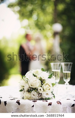 Wedding bridal bouquet with white roses on the table in the garden against the background of the bride and groom. Wedding concept - stock photo