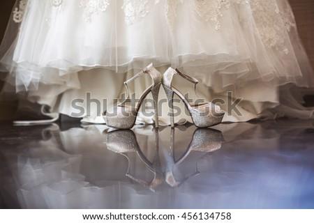 Wedding, bridal shoes with diamonds, background - dress of bride - stock photo