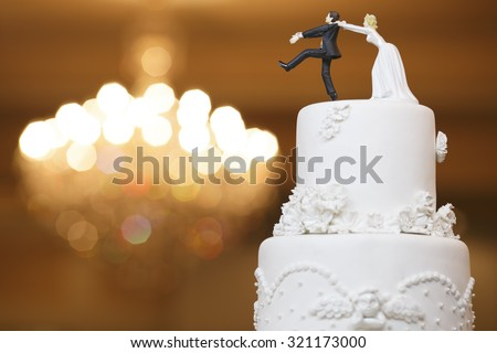 wedding bride and groom couple doll in funny action on wedding cake - stock photo
