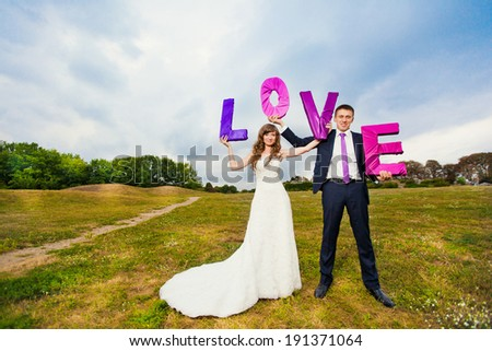 Wedding. Bride and groom. Inscription love on the grass. - stock photo
