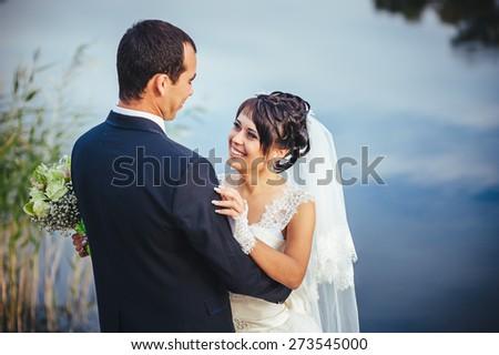 wedding: bride and groom on the seashore. Honeymoon. The bride and groom hugging on the shore of Lake. groom and bride hugging on a green lake. Groom and Bride in a park. wedding dress. Bridal wedding - stock photo