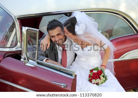 Wedding, bride and groom with a vintage car - stock photo