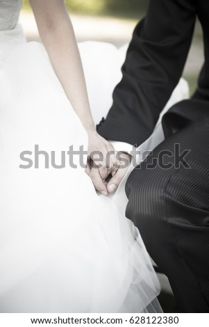 Wedding bride in bridal gown dress and groom in suit holding hands in marriage ceremony.
