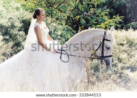 Wedding. Bride on white horse in white flowers