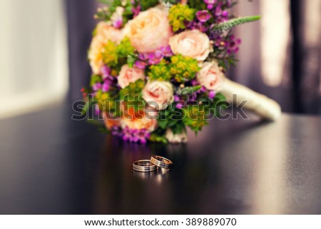Wedding bunch. Focus on a  wedding rings against a bridal bouquet from roses