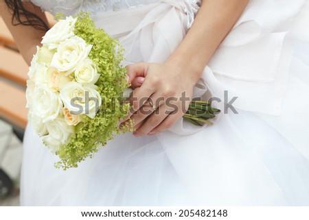 Wedding bunch of flowers in hands of the bride  - stock photo