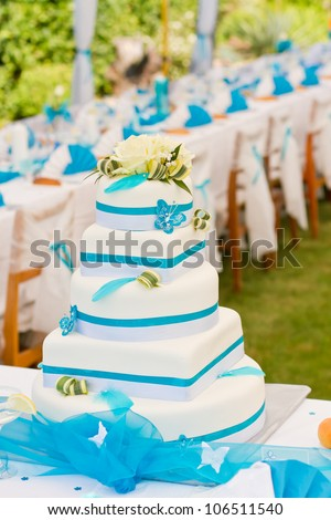 Wedding cake and luxury table setting in white and blue colors - stock photo