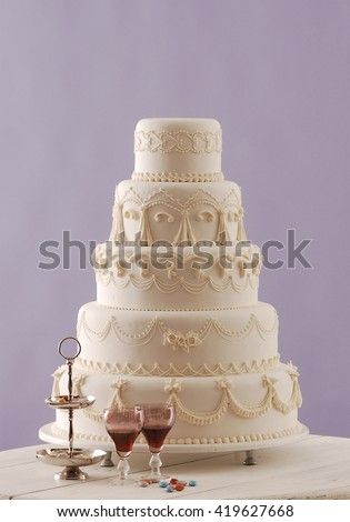 wedding cake and red wine behind purple wallpaper - stock photo