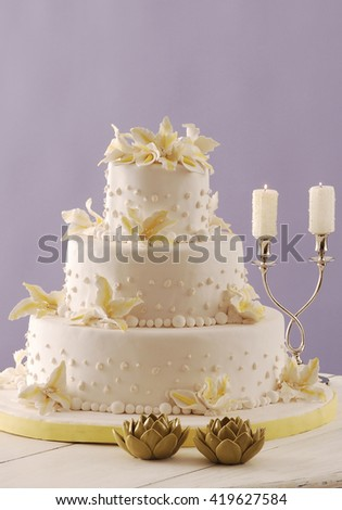 wedding cake and silver candlestick behind purple wallpaper - stock photo