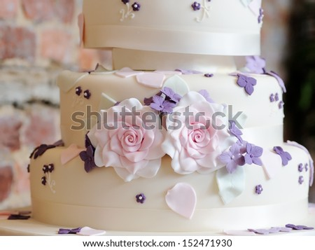 Wedding cake closeup with pink and purple flowers decorating at reception - stock photo