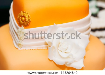 Wedding cake covered in orange and white rolled fondant and decorated with marzipan flowers - stock photo