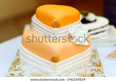 Wedding cake covered in white rolled fondant and decorated with marzipan flowers - stock photo