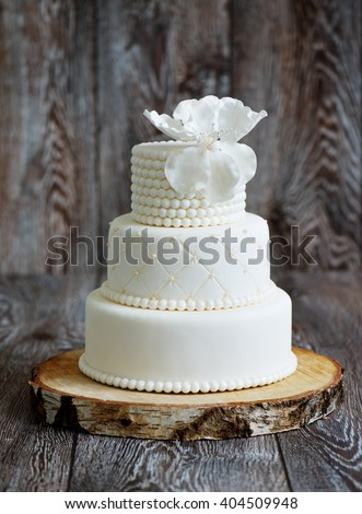 Wedding cake covered with white fondant, decorated with beads and hand-made flower on top