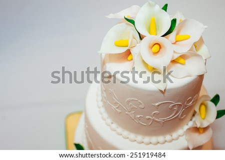 wedding cake decorated with flowers. Wedding cake with white icing and bow. Wedding luxurious  restaurant decoration. Table setting at a luxury wedding reception. - stock photo
