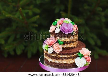 Wedding cake. Naked Wedding cake with flowers - stock photo
