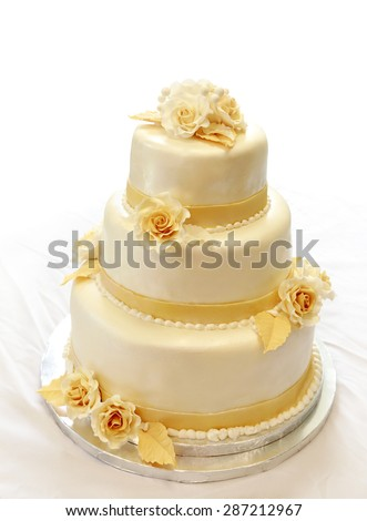 Wedding cake, on white (not isolated) background. 3-tiers covered in ivory fondant sprayed with pearl spray and yellow/gold roses made of sugar paste.