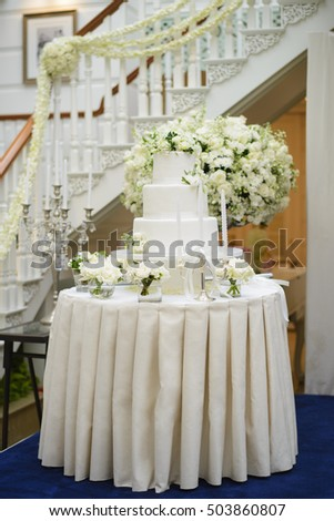 Wedding cake surrounded by white flowers at reception