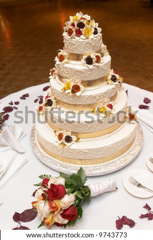 Wedding cake with bouquet of yellow and red roses