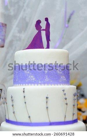 Wedding cake with figurines on top - stock photo