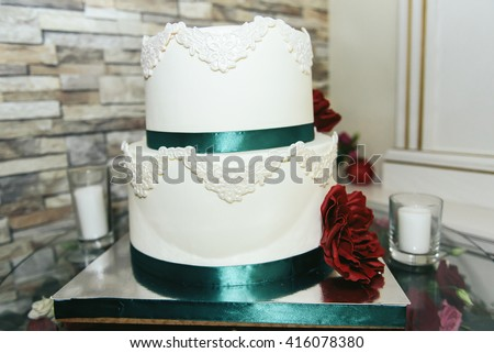 Wedding cake with green ribbon and red flower - stock photo