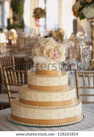 Wedding cake with roses at luxury reception - stock photo