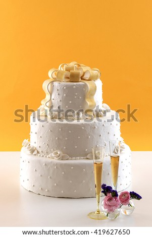 wedding cake with white wine glass behind orange wallpaper - stock photo