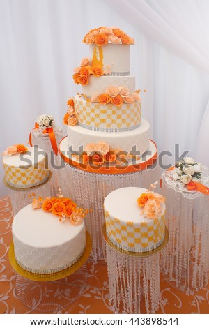 Wedding cakes big beautiful tasty many-tier decorated with orange flowers on white background