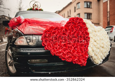 Wedding car decorated with two hearts made of flowers roses. - stock photo