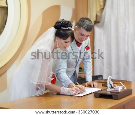 Wedding ceremony. Bride and groom signing marriage license or wedding contract