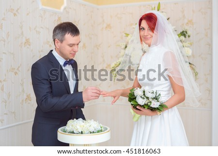 Wedding ceremony.  Groom puts ring on bride's finger