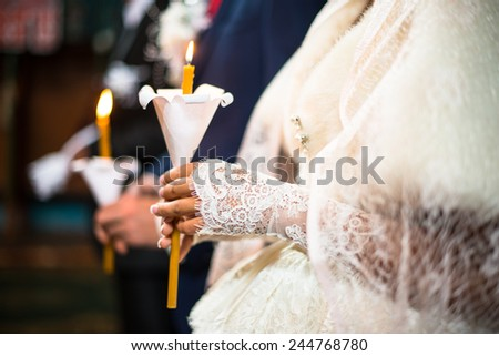 Wedding ceremony in orthodox church. Bride and groom holding the candles. Close up. - stock photo