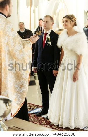 wedding ceremony of happy elegant blonde bride and stylish groom, holding hands in the old church - stock photo